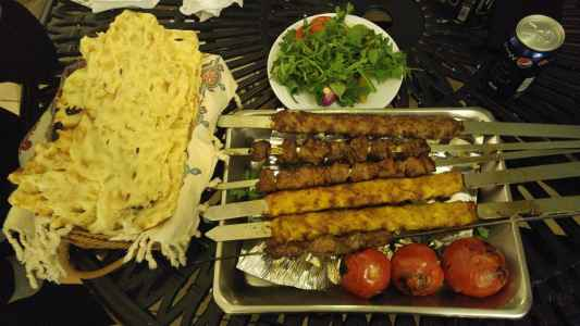 Kebabs with tomato and fresh greens